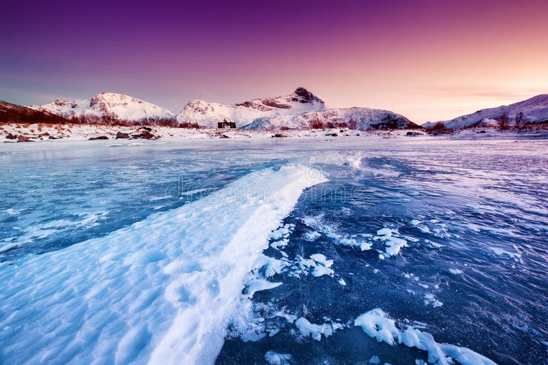 Mountain ridge and ice on the frozen lake surface. Natural landscape on the Lofoten islands, Norway. royalty free stock photos