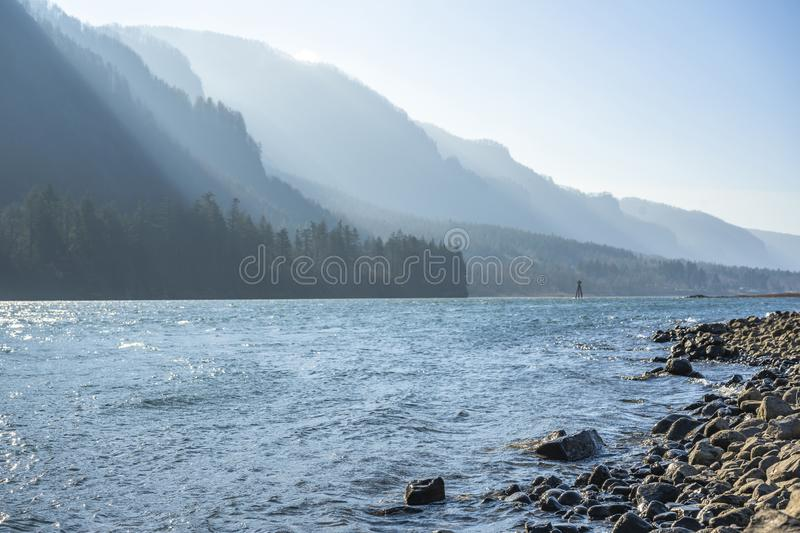 Mountain ridge illuminated by the slanting rays of the sun on the stony bank of the Columbia River in Colombia Gorge. Landscaping with mountain range with forest royalty free stock image