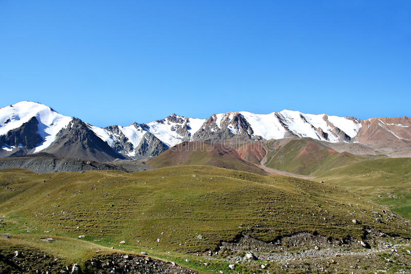 Mountain ridge with snow, North Tien-Shan. Mountain ridge with snow against a blue sky without clouds. North Tien-Shan mountains royalty free stock photo