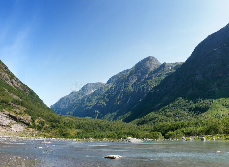 Mountain river formed by meltwater of glacier stock photo