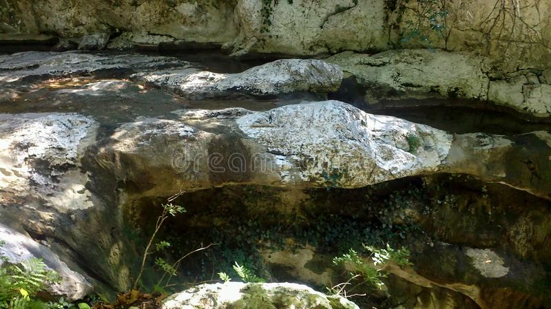 The mountain river has dried up. A river flows between the rocks, it is almost dry, huge stones can be seen royalty free stock photos