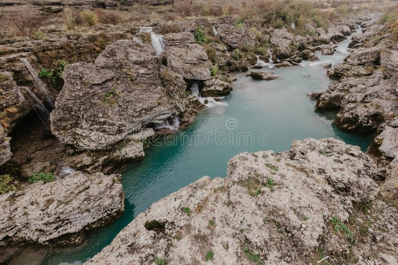 Mountain river with huge, big, and small stones and rocks on riverbed.  royalty free stock image
