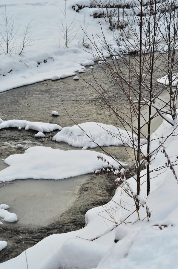 Mountain river with snow in winter. River in winter time covered with snow, winter landscape stock photography