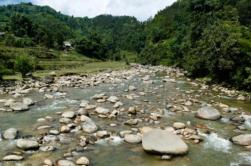 Mountain river with stones in water. Cold water flowing along small villages and rice fields. Valley view near Sa Pa, Vietnam stock photography