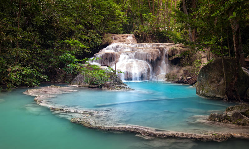 Mountain river stream flows through tropical forest and falls stock photo