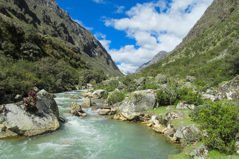 Mountain river stream. Grass and stones riverbank royalty free stock photo