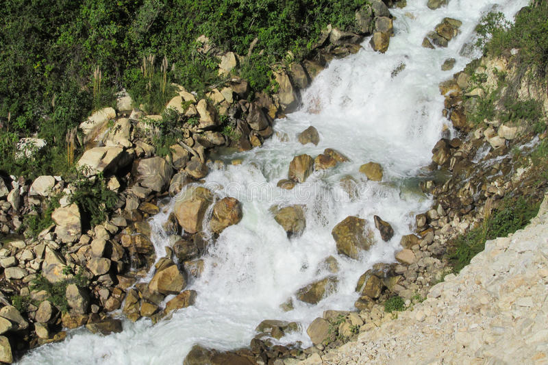 Mountain river stream. Waterfall, grass and stones riverbank stock photography