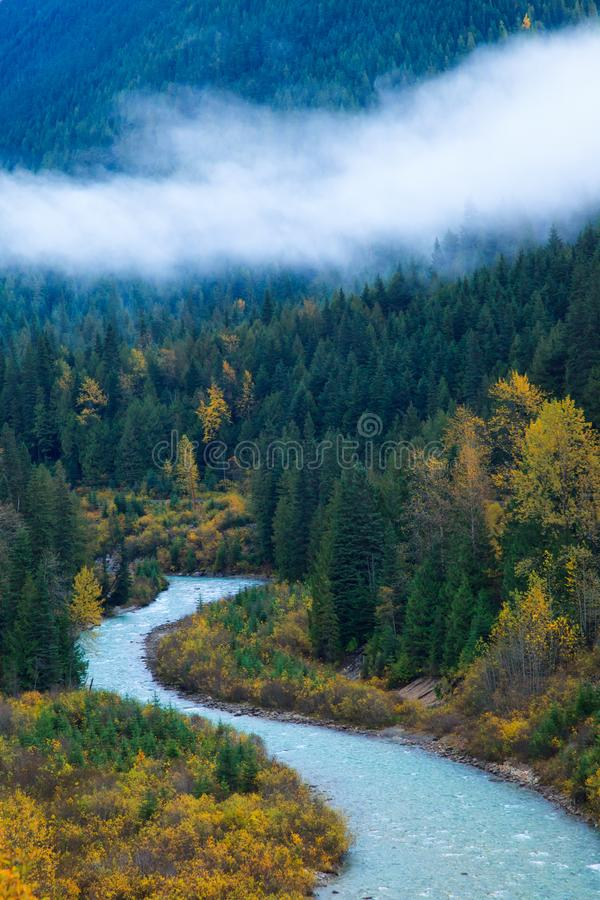 A mountain river surrounded by colorful autumn trees and low clouds stock image