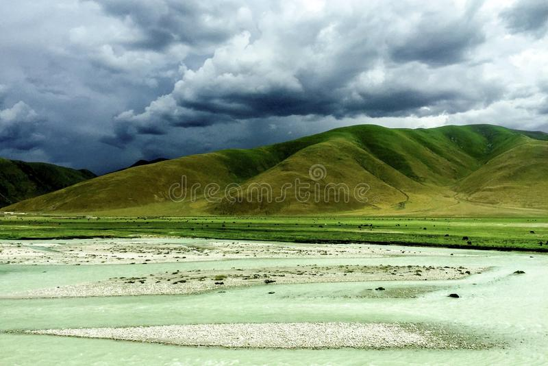 mountain and river under dark clouds royalty free stock image