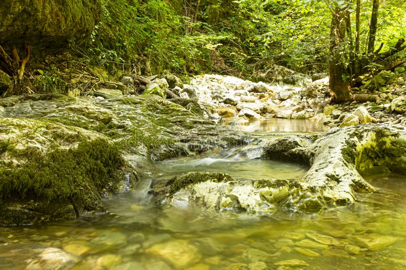 Mountain river water flowing over rocks. Mountain river water flowing over rocks closeup in sunny summer day royalty free stock images