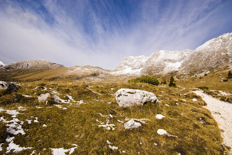 Mountain Road. Spring mountain landscape with hiking road with yellow grass, snow and mountains in a sunny day - shot from an ultra wide angle - Malghe del royalty free stock images