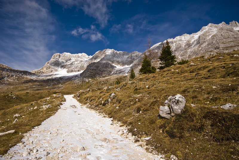 Mountain Road. Spring mountain landscape with hiking road with yellow grass, snow and mountains in a sunny day - shot from an ultra wide angle - Malghe del stock photography