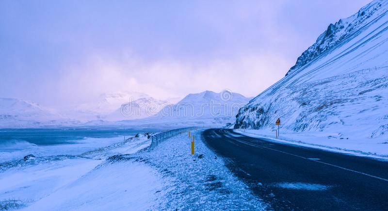 Mountain road along the coast in Snaefellsnes at stormy weather in winter, western Iceland stock photo