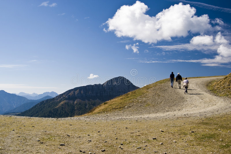 Mountain road in Austria. Hiking on a mountain trail with people in a sunny day with blue sky - Austria 2007 stock photo