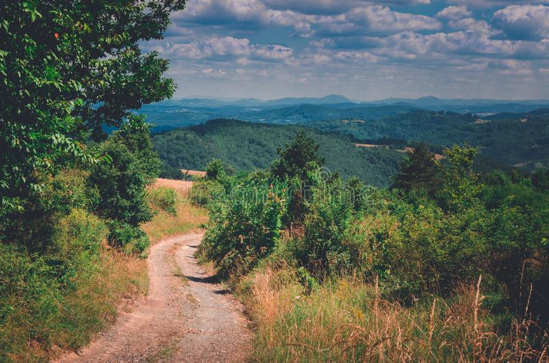 Mountain road with a beautiful view into the distant mountains and cloudy skies. Mountain country road with a beautiful view into the distant mountains and royalty free stock photography
