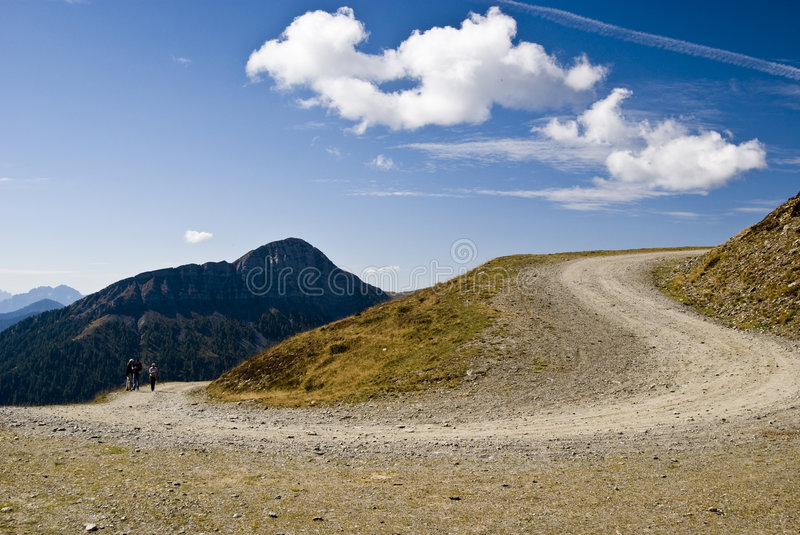 Mountain Road Curve. Mountain trail curve in a sunny day with blue sky and clouds - Austria 2007 royalty free stock photography