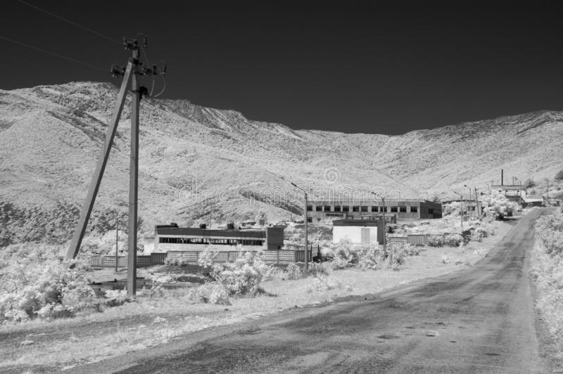 Mountain road down to the power substation. IR photo royalty free stock photo