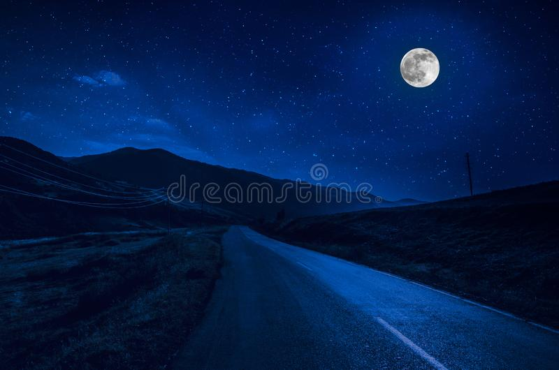 Mountain Road through the forest on a full moon night. Scenic night landscape of dark blue sky with moon. Azerbaijan royalty free stock photography