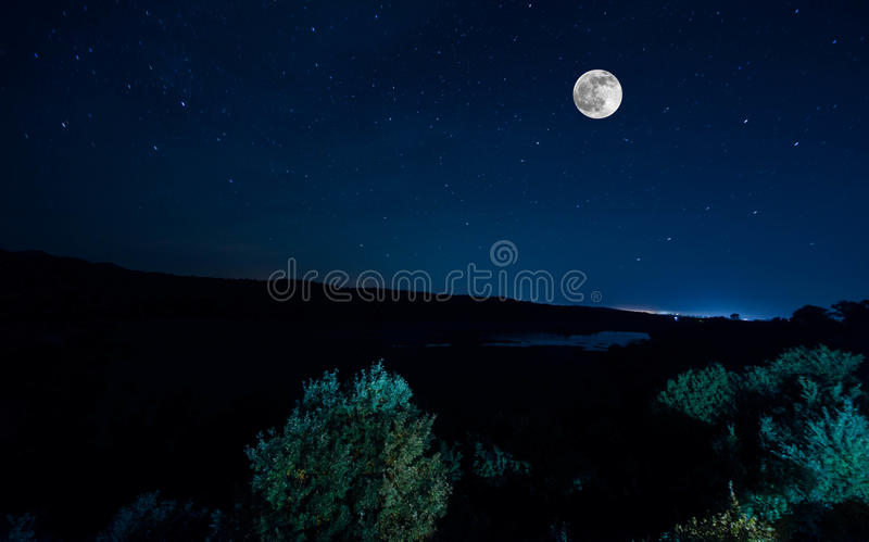 Mountain Road through the forest on a full moon night. Scenic night landscape of dark blue sky with moon. Azerbaijan. Long shutter royalty free stock image
