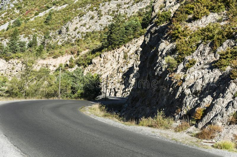 Mountain road in southeastern France. Mountain road between forests in Alpes-de-Haute-Provence department in southeastern France. Neighborhoods of a medieval stock photo