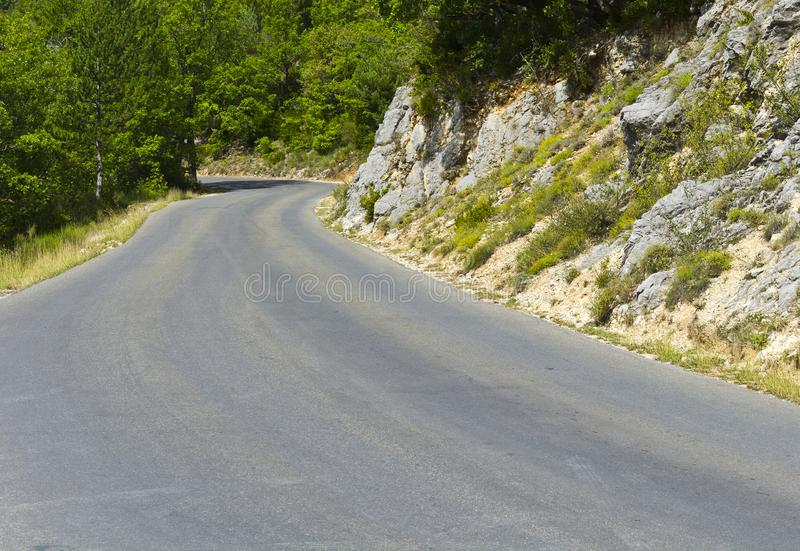 Mountain road in southeastern France. Mountain road between forests in Alpes-de-Haute-Provence department in southeastern France. Neighborhoods of a medieval stock photography