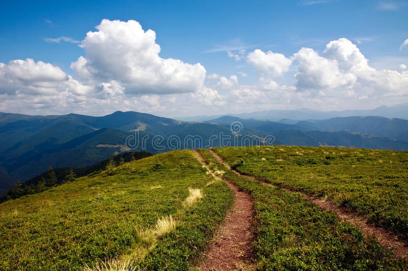 Mountain road leading to the horizon under a blue sky stock images