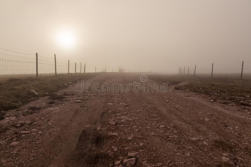 A mountain road in the midst of fog at dawn, with warm colors an stock photo