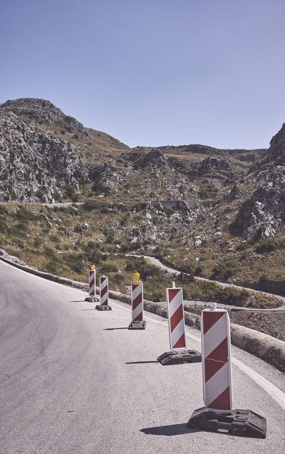 Mountain road with portable warning traffic signs stock images