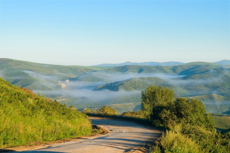 The mountain road from Serebryansk to Ust-Kamenogorsk in the early morning East Kazakhstan region, Kazakhstan. The roads of the East Kazakhstan region are quirky stock image