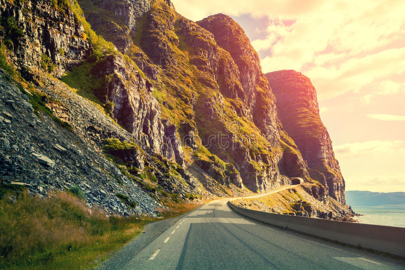 Mountain road at sunset. The road along the fjord stock image