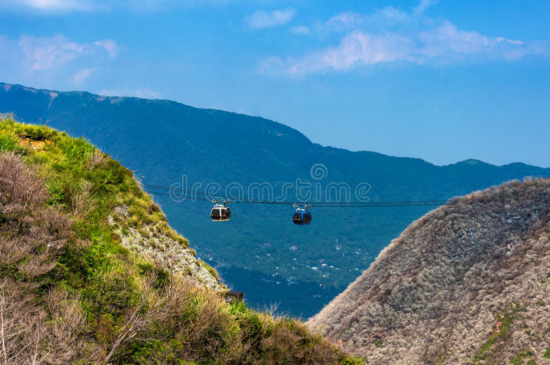 Mountain ropeway, cable car. With slopes covered with green trees and fog, mist. Owakudani, Hakone, Japan royalty free stock images