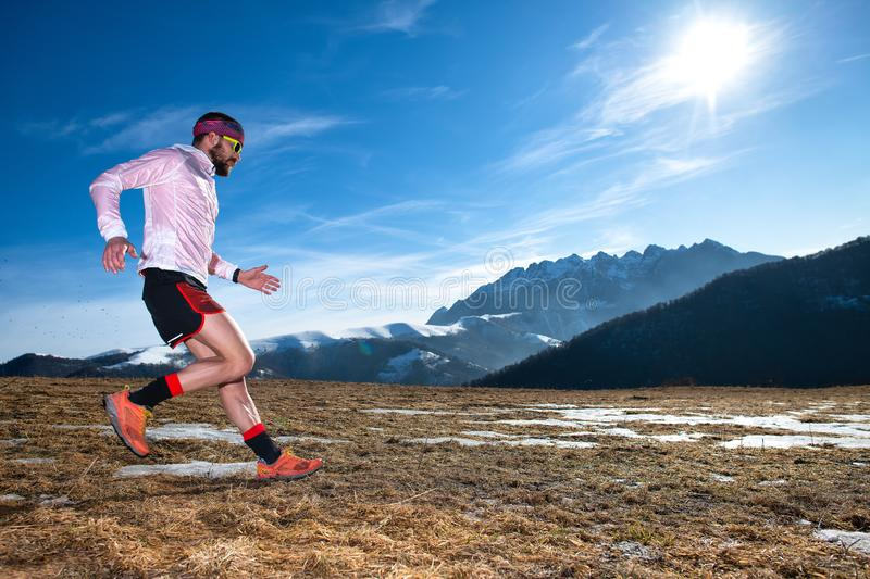 Mountain runner in downhill action on slippery ground stock photography