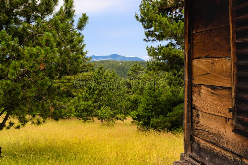 Mountain scenery behind old wooden cottage stock photo