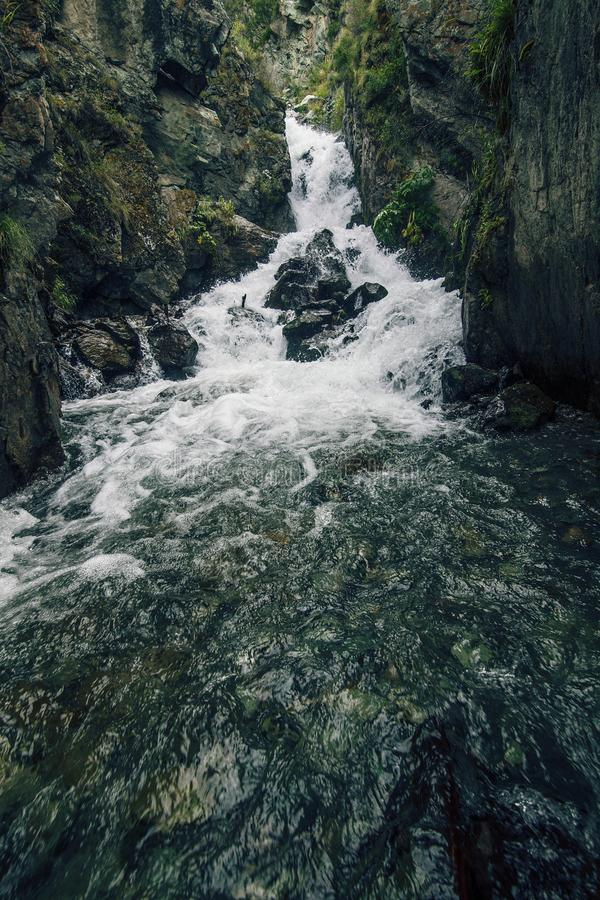 Mountain scenic unspoiled waterfall with ice water flowing over stock photo