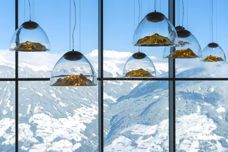 Mountain-shaped lamps hang inside a restaurant opposite a snow-capped mountains window in Austrian Alps.Selective focus on lamps royalty free stock images