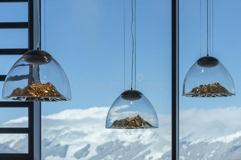 Mountain-shaped lamps hang inside a restaurant opposite a snow-capped mountains window in Austrian Alps.Selective focus on lamps stock photography