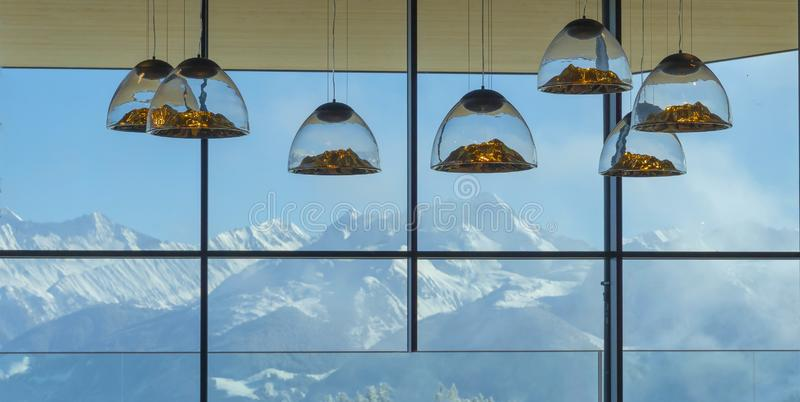 Mountain-shaped lamps hang inside a restaurant opposite a snow-capped mountains window in Austrian Alps.Selective focus on lamps stock image
