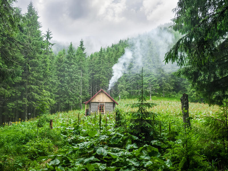 Mountain shelter in Carpathians during inclement weather. Small wooden mountain shelter in a small clearing in the forest during inclement weather. Carpathians stock images