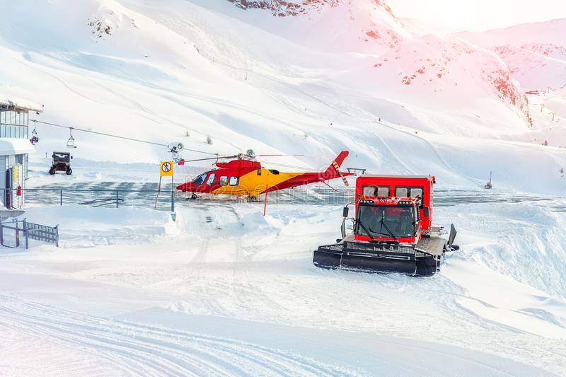 Mountain ski life rescue station with heavy machinery. Helicopter, snowcat and snowmobile standby ready to save tourist in royalty free stock image