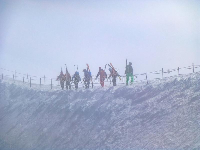 Mountain skiers go together on mountain ridge in snow storm and danger of avalanche, mountain peak Aiguille du Midi in France stock image