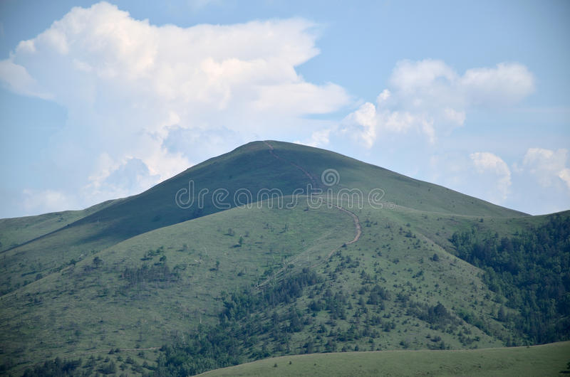 Mountain and sky. Mountain with a path beneath blue sky stock photo