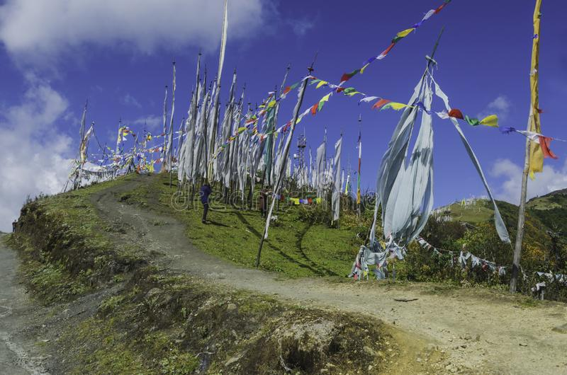 The mountain slope in the Chele la pass surrounded by the prayer flags. The mountain slope in the Chele la pass in Bhutan, way towards the cliff, surrounded by stock images