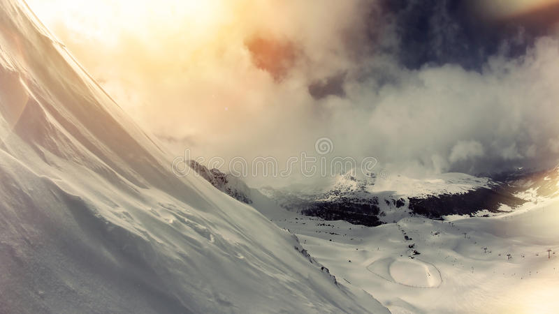 Mountain slope, a lot of snow, the view through the clouds. Winter landscape. stock photo