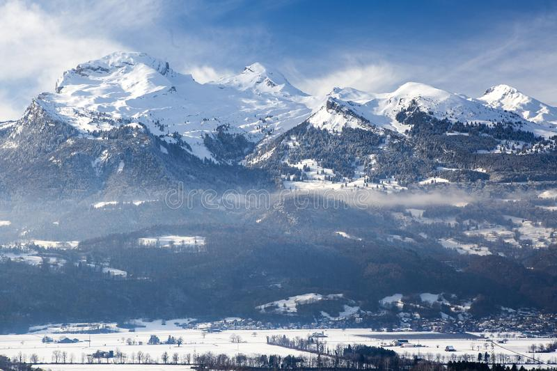 The mountain in the snow and a town in the Alps in winter stock photography