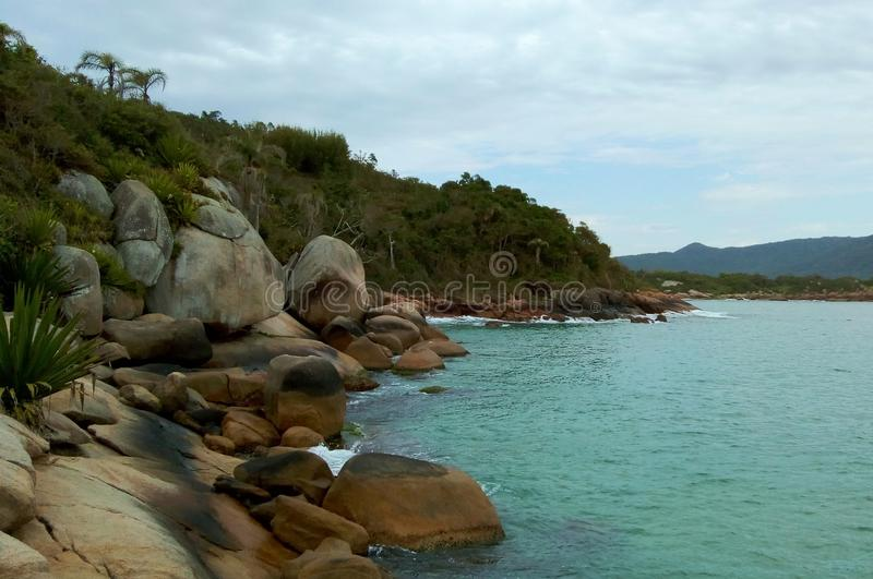 Stones and vegetation by the Barra da Lagoa beach. A mountain, some stones and a crystal clear blue water on the beach compose a beautifull landscape at Barra da royalty free stock photos