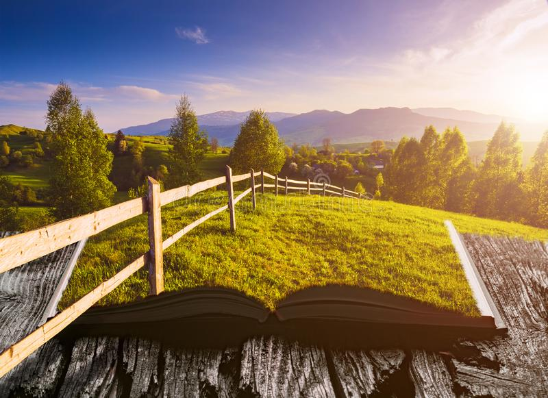 Mountain spring valley on the pages of book. Mountain spring valley covered with fresh green grass on the pages of an open magical book. Majestic landscape royalty free stock photo