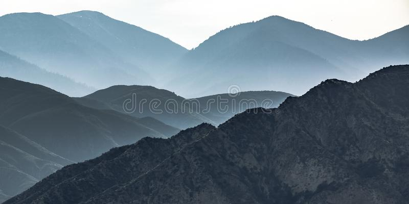 Mountain with steep slopes in Ontario California. Expansive view of a wide mountain range beneath a bright sky in Ontario, California. The mountain have steep stock images