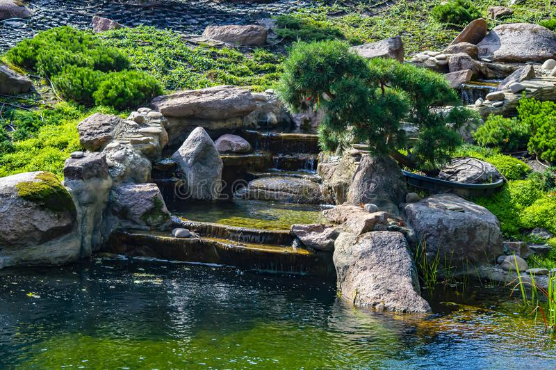 A mountain stream flows down the stones into the lake royalty free stock images