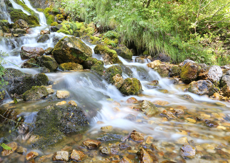 Mountain stream with water that seems in motion photographed wit. Wonderful mountain stream with water that seems in motion photographed with a long exposure stock photography