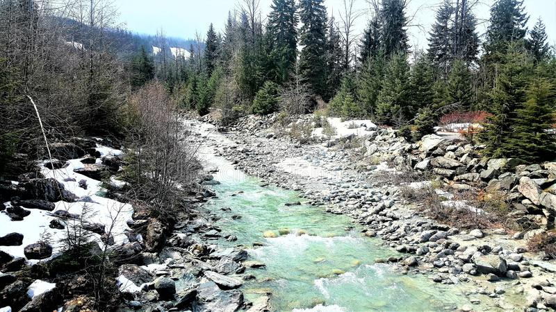 Mountain Stream in Whistler Canada. Mountain stream viewed from a bridge in Whistler, Canada, in March stock photo